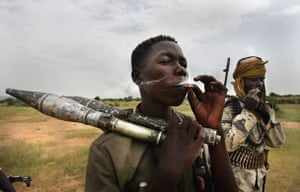 Darfur atrocities: Rebel fighters from the Sudanese Justice and Equality Movement (JEM) smoke