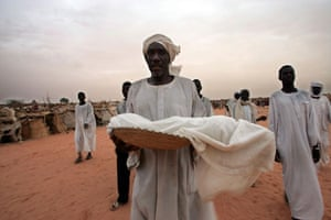 Darfur atrocities: A father carries his son's body at a refugee camp in Darfur