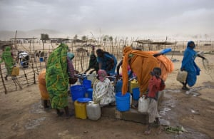 Darfur atrocities: Refugees from Darfur gather water at a well in eastern Chad.