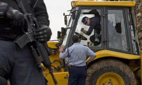 Police examine a bulldozer used to ram a police car in Jerusalem