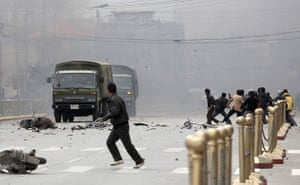 Tibetan uprising: 14 March 2008: Tibetans throw stones at army vehicles on a street in Lhasa
