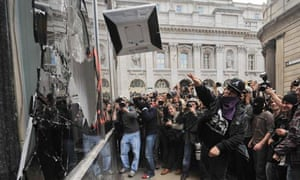 A G20 protestor throws a computer terminal at a branck of RBS