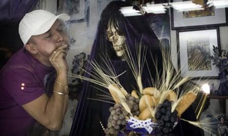A man puffs smoke towards a skeletal figure known in Mexico as Santa