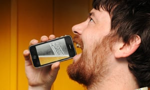 A man with a Carling iPint virtual lager app on an iPhone