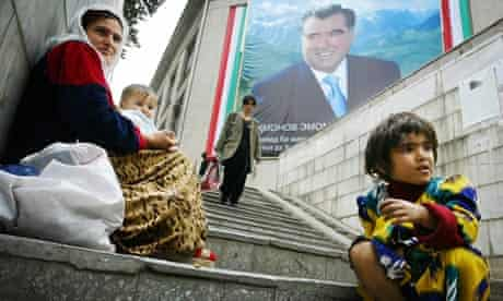 A mother and her children beg in front of picture of a picture of Tajik President Emomali Rakhmonov