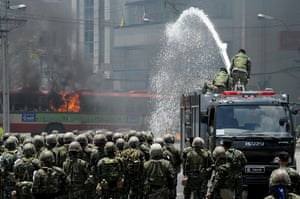 Thailand protests: Thai soldiers use a water canon to douse flames coming from a bus.