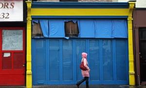 A woman walks past empty boarded up shops
