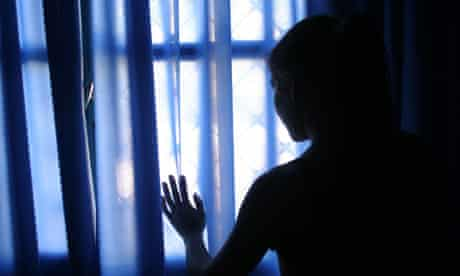A prostitute in Asuncion, Paraguay looks out the window of the brothel where she works