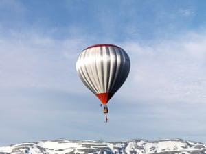 Eskil Ronningsbakken: Ronningsbakken balancing on a trapeze below a hot air balloon above Voss