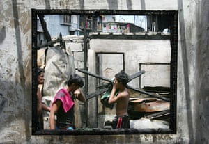 24 hours in pictures: Manila, Philippines: Local residents are framed in a burnt window frame.