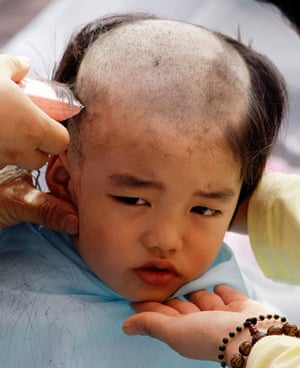 24 hours in pictures: Seoul, South Korea: A boy has his head shaved by a monk.