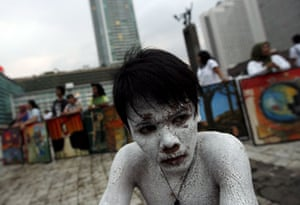 24 hours in pictures: Jakarta, Indonesia: An activist wearing body paint performs for earth day.