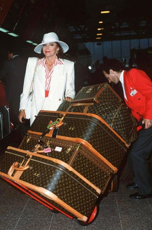Joan Collins style icon: Joan Collins wearing a white suit and hat with Louis Vuitton luggage