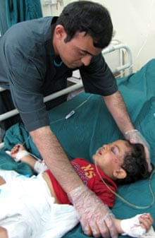 An injured child is treated after a suicide bomber attacked humanitarian aid workers in Baghdad