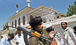 An armed Pakistani Taliban talks with residents outside a mosque in Buner