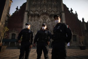 Swine flu : Police officers wearing masks outside a  cathedral  in Mexico City