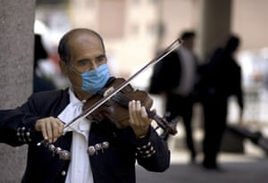 Swine flu : A Mariachi wears a mask as he plays the violin in Mexico City