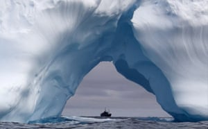 The Steve Irwin as seen through the arch of an iceberg as it sails through the Southern Ocean