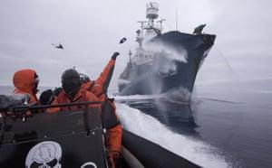 Sea Shepherd crew member Laurens De Groot hurls a bottle of butyric acid