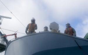 Crew members aboard the Yushin Maru No 3 gesture towards Sea Shepherd activists