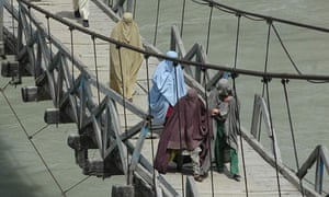 People flee across a bridge in Pakistan's Lower Dir district, where troops are fighting the Taliban