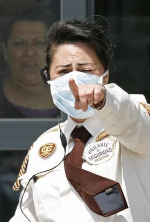 International Swine Flu: A guard wearing a mask outside the Hospital General in Almansa, Spain