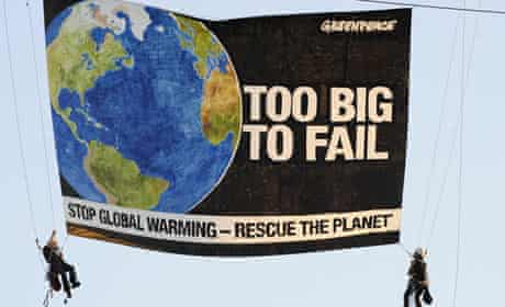 Greenpeace activists display a banner from a crane near the State Department in Washington