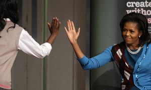 Michelle Obama gives a pupil a high-five during a visit to Elizabeth Garrett Anderson Schoo