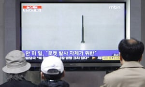 South Koreans watch news of North Korea's rocket launch on television at Seoul railway station.