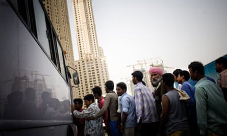 Migrant workers line up for a bus after a day of work in Dubai