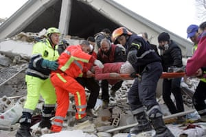 Italy earthquake: Firefighters carry a woman out of a crumbled home