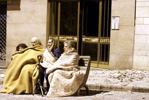 Earthquake in Italy: Elderly women sit in a street next to rubble
