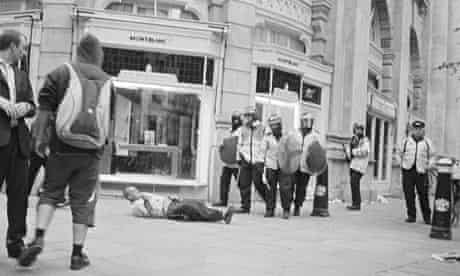 Ian Tomlinson lies on the ground in the City