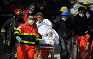 earthquake in Italy: Rescuers with an injured man who was recovered from a collapsed building