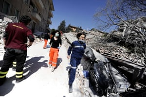 earthquake in Italy: Doctors and rescue workers rush by a collapsed building