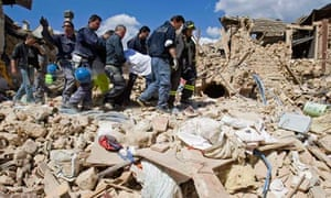 Italian rescue workers carry body from rubble after an earthquake in the Italian village of Onna