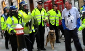 Ian Tomlinson walks past police dog handlers during the G20 protests
