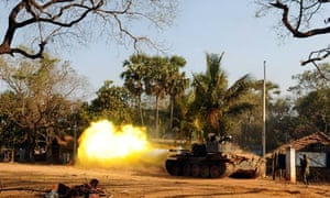 A Sri Lankan soldier stands near a tank as it fires a shell at Puthukkudiyiruppu