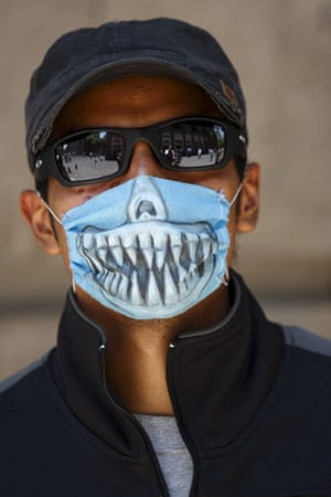 Swine flu face masks: A man wears a decorated face mask against swine flu in Mexico