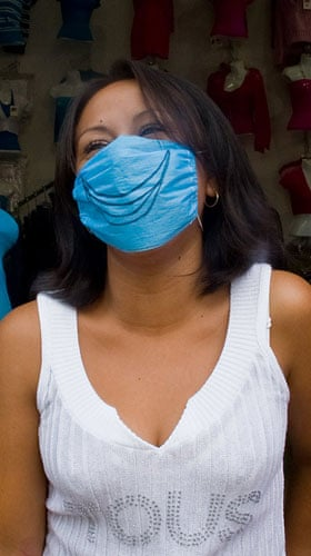 Swine flu face masks: A shop assistant wears a surgical mask to avoid swine flu in Mexico City