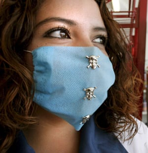 Swine flu face masks: A woman wears a protective mask decorated with skulls, in Leon, Mexico