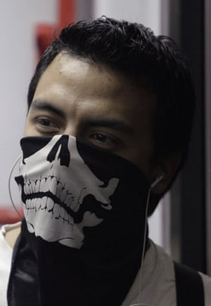 Swine flu face masks: A man wearing a face mask decorated with a skull