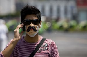 Swine flu face masks: A man wears a decorated protective mask as he talks on his mobile phone