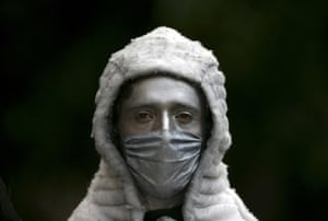 Swine flu face masks: A street performer wears a surgical mask painted silver in Mexico City