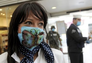 Swine flu face masks: A woman wears a surgical mask with a butterfly painted on it.
