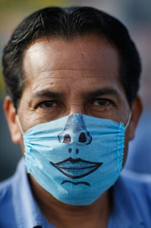 Swine flu face masks: A drawing-adorned surgical mask worn by a man in Mexico City