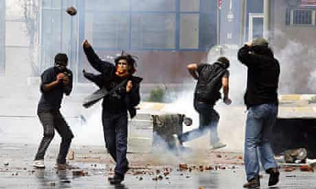 Protesters throw stones at riot police during a May Day rally in Istanbul.