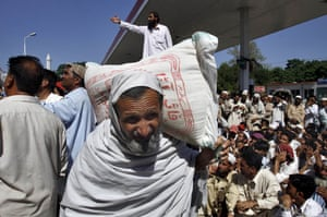 Pakistan Swat exodus: A man internally displaced from Swat Valley carries a sack at a relief camp
