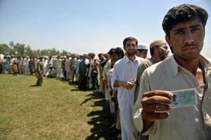 Pakistan Swat exodus: An internally displaced Pakistani man holds up an identity card