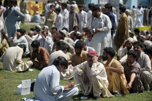 Pakistan Swat exodus: A Pakistani UNHCR official registers displaced men at a makeshift camp.